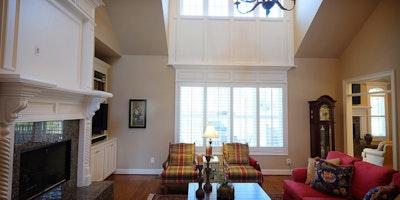 Large living area with vaulted ceilings, white trim, hardwood floors, tall windows