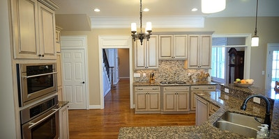 Light tan, taupe large kitchen with white trim and hardwood floors - Residential painting