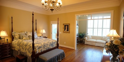 Light tan, taupe bedroom with sitting area, crown molding, white trim, hardwood floors