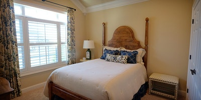 Light tan, taupe bedroom with vaulted ceilings and large window, white trim - Residential painting