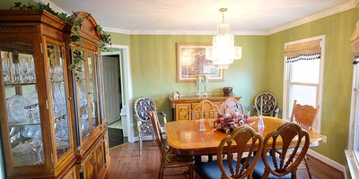 Light green walls with white crown molding, hardwood floors and oak dining room set