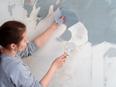Woman removing wallpaper at a home in Nashville