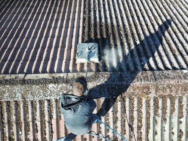 Nash Painting employee cleaning black streaks on a roof