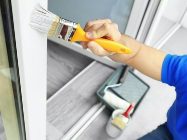 Local painter painting a white windowsill