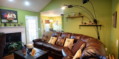 Green room with leather sectional & fireplace - Residential painting by Nash Painting Nashville