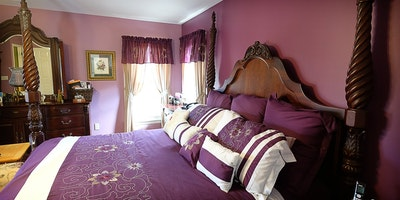 Mauve rose color walls with matching four poster king size bedding and window treatments