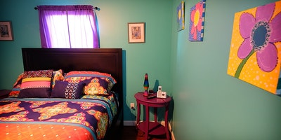 Teal walls against colorful bedding and flower canvas wall art - Residential painting